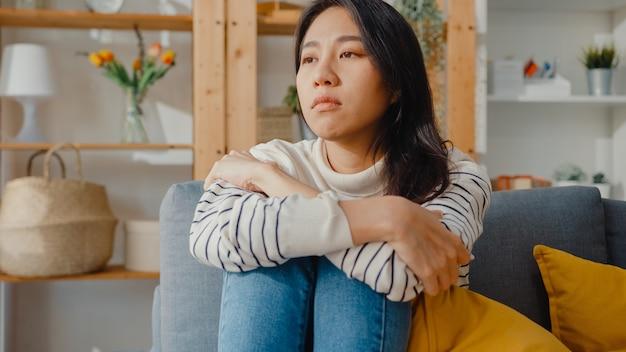 Nachdenkliche asiatische dame sitzen mit einem gefühl der einsamkeit, fühlen sich deprimiert und verbringen zeit alleine zu hause zu bleiben