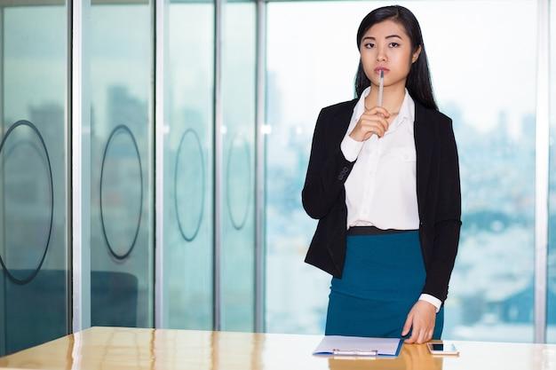 Nachdenkliche attraktive asiatische geschäftsfrau am schreibtisch