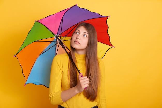 Nachdenkliche attraktive frau, die mehrfarbigen regenschirm hält und beiseite schaut, mädchen mit langen schönen haaren