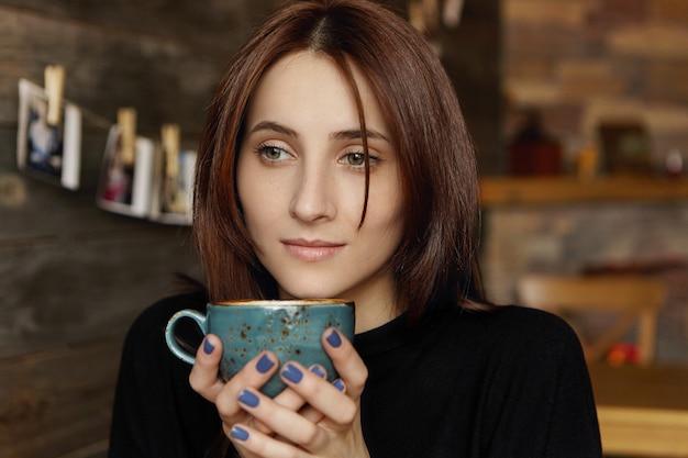 Nachdenkliche attraktive junge europäische frau mit braunem schokoladenhaar, die elegantes schwarzes kleid hält, das tasse cappuccino hält, tagträumen, heißes und frisches getränk genießt, während im gemütlichen café sitzt