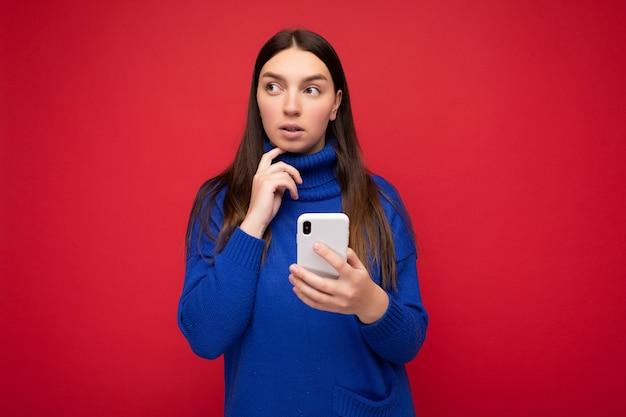 Nachdenkliche attraktive positive gut aussehende junge brünette frau, die stilvollen blauen warmen pullover trägt