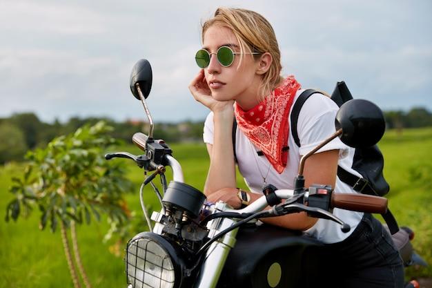 Nachdenkliche bikerin trägt stilvolle sommerbrillen, ein kopftuch und ein t-shirt, trägt einen rucksack, sitzt auf ihrem schnellen motorrad und fährt durch die grüne natur