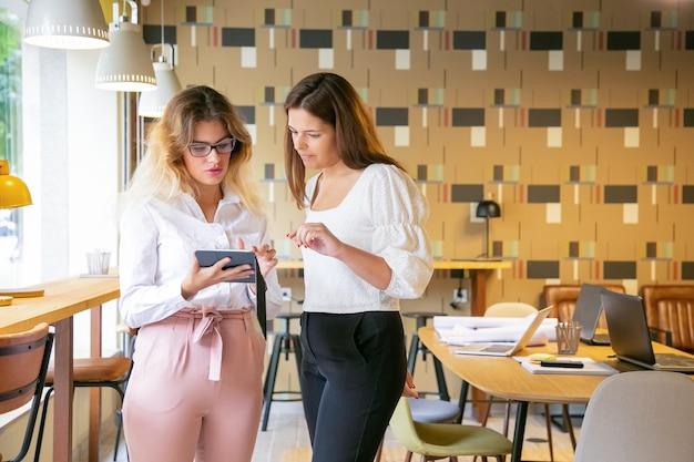 Nachdenkliche blonde frau, die tablette hält und design auf bildschirm zum kunden zeigt