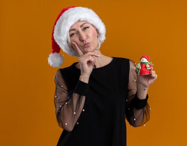 Nachdenkliche blonde frau mittleren alters, die weihnachtsmütze hält, die kleine schneemannstatue hält, die kamera hält hand auf kinn lokalisiert auf orange hintergrund hält