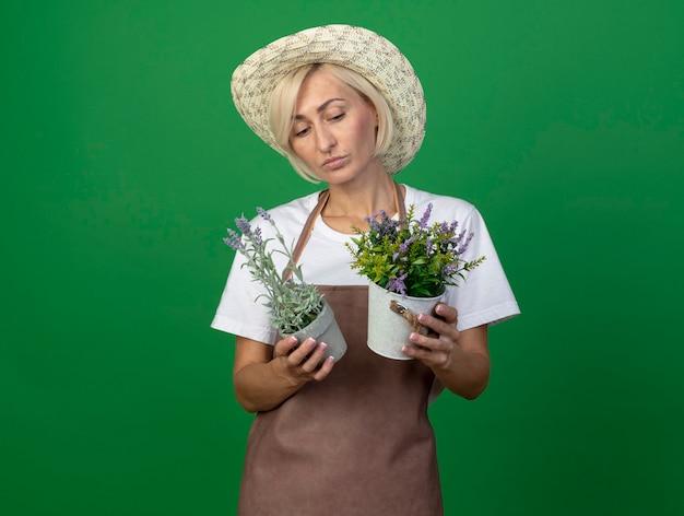 Nachdenkliche blonde gärtnerin mittleren alters in uniform mit hut, die blumentöpfe hält und betrachtet, die auf grüner wand mit kopienraum isoliert sind