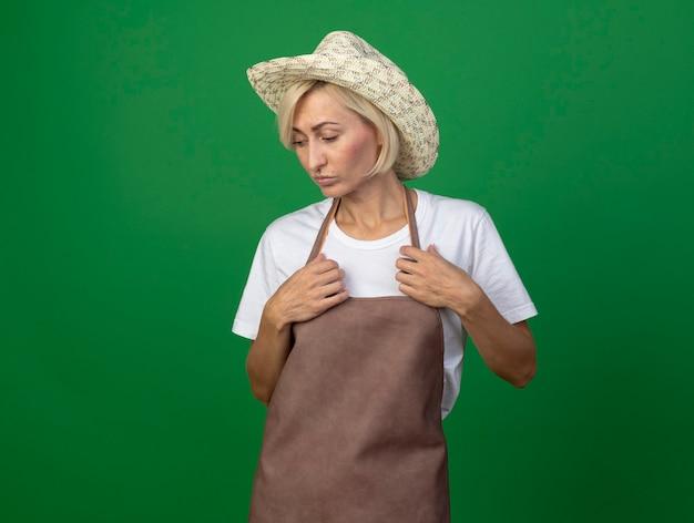 Nachdenkliche blonde gärtnerin mittleren alters in uniform mit hut, die ihre uniform berührt und nach unten schaut