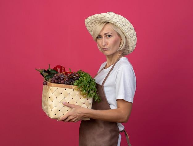 Nachdenkliche blonde gärtnerin mittleren alters in uniform mit hut, die in der profilansicht steht und einen korb mit gemüse isoliert auf purpurroter wand mit kopierraum hält