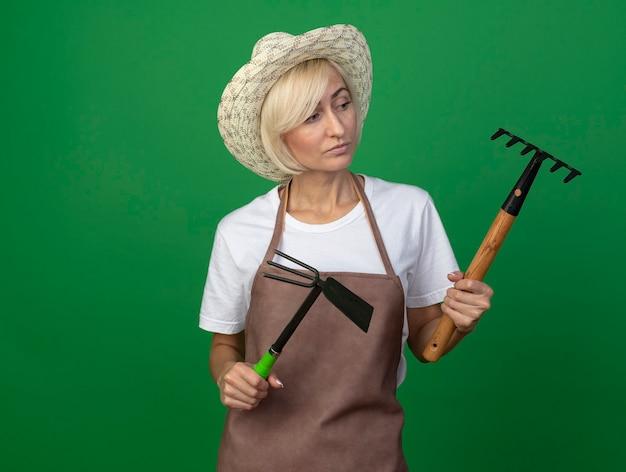 Nachdenkliche blonde gärtnerin mittleren alters in uniform mit hut mit rechen und hacke, die rechen anschaut