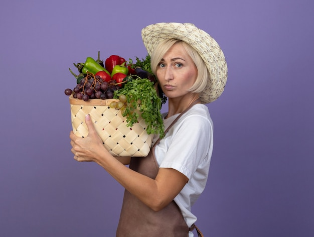Nachdenkliche blonde gärtnerin mittleren alters in uniform mit hut