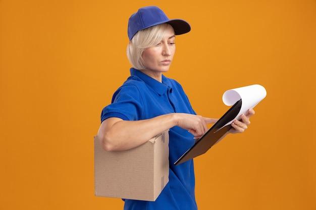 Nachdenkliche blonde lieferfrau in blauer uniform und mütze, die in der profilansicht steht und karton unter dem arm und zwischenablage hält und auf die zwischenablage schaut und den finger darauf legt