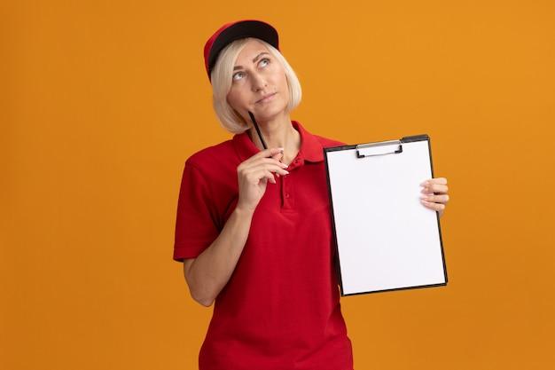 Nachdenkliche blonde lieferfrau mittleren alters in roter uniform und mütze, die die zwischenablage hält und das gesicht mit bleistift berührt, der isoliert auf orangefarbener wand mit kopierraum aufschaut
