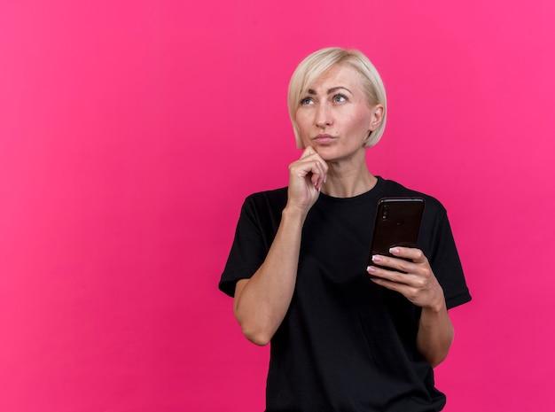 Nachdenkliche blonde slawische frau mittleren alters, die handy hält, das kinn berührt, lokalisiert auf purpurrotem hintergrund mit kopienraum