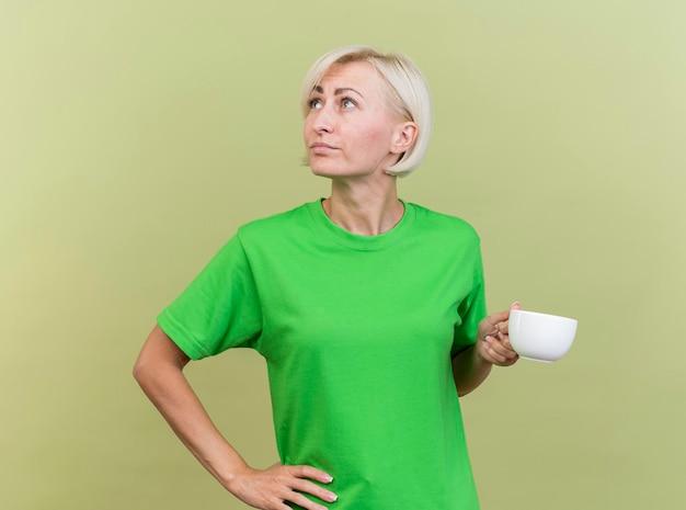 Nachdenkliche blonde slawische frau mittleren alters, die tasse tee hält, die hand auf taille hält, die seite lokalisiert auf olivgrüner wand betrachtet