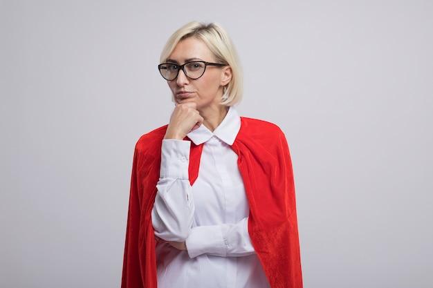Nachdenkliche blonde superheldin mittleren alters in rotem umhang mit brille, die hand auf das kinn legt, isoliert auf weißer wand mit kopierraum