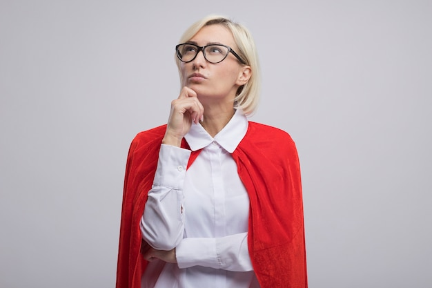 Nachdenkliche blonde superheldin mittleren alters in rotem umhang mit brille, die hand auf das kinn legt und nach oben schaut