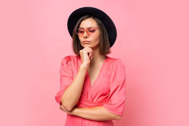 Nachdenkliche brünette frau in der stilvollen brille, die über rosa wand aufwirft.