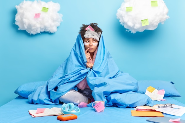Nachdenkliche dunkelhäutige frau schaut zur seite und versucht zu entscheiden, dass etwas, das in weiche deckenposen auf dem bett gewickelt ist, ideen auf aufkleber und notizbuch schreibt