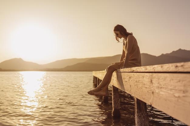 Nachdenkliche einzelne kaukasische hübsche junge frau, die auf einem pier eines sees sitzt, der unten auf das wasser bei sonnenuntergang schaut - vintage orange farbstimmung