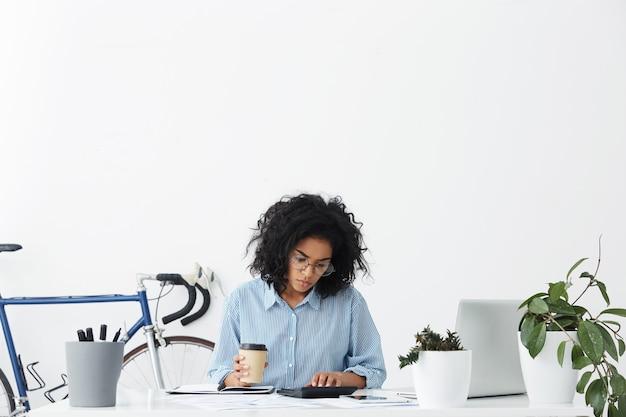 Nachdenkliche ernsthafte professionelle arbeiterfrau, die im büro sitzt