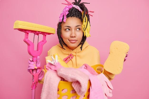 Nachdenkliche ethnische hausfrau mit nachdenklichem blick hält saubere werkzeuge über rosa wand