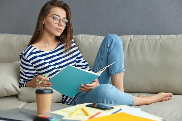 Nachdenkliche europäische frau in transparenten gläsern, hält lehrbuch und stift, schreibt notizen als vorbereitung für das weitergeben von kurspapier, trinkt kaffee zum mitnehmen, posiert auf der couch in der wohnung. arbeitskonzept