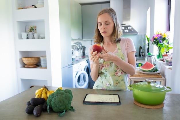 Nachdenkliche fokussierte frau, die obst beim kochen in der küche hält, mit tablette nahe topf und frischem gemüse auf theke. vorderansicht. kochen zu hause und gesundes essen konzept