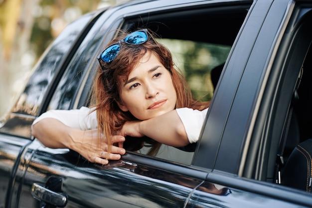 Nachdenkliche frau, die durch autofenster schaut