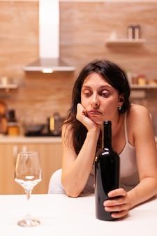 Nachdenkliche frau, die eine weinflasche hält, die wegen der trennung depressiv ist.