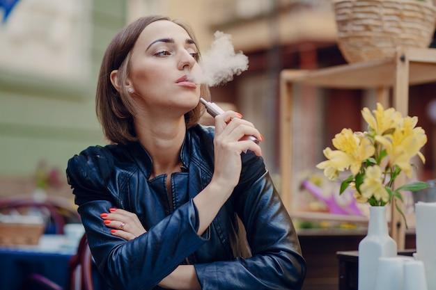 Nachdenkliche frau, die ihre elektronische zigarette genießen