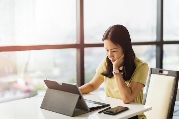Nachdenkliche frau, die im büro am tablet-computer arbeitet working