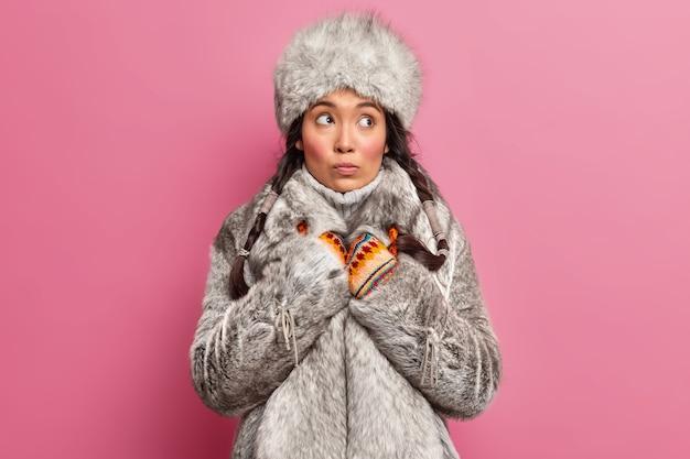 Nachdenkliche frau, die im hohen norden lebt, trägt warme winterkleidung und schaut weg, lebt in tundra-posen an einer rosigen wand