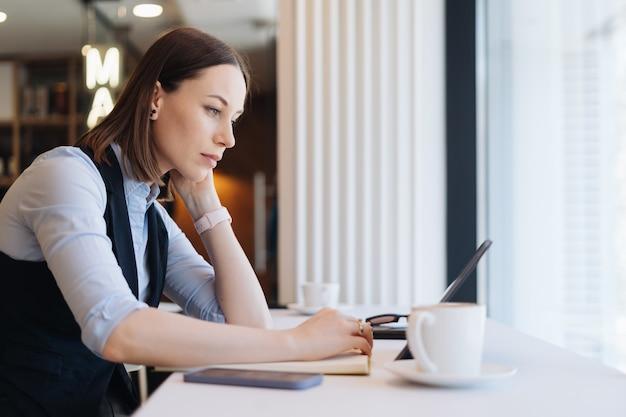 Nachdenkliche frau, die in der cafeteria mit einer kaffeetasse sitzt, während tablette schaut. frau mittleren alters, die tee trinkt, während sie denkt. entspannen und nachdenken beim kaffeetrinken.