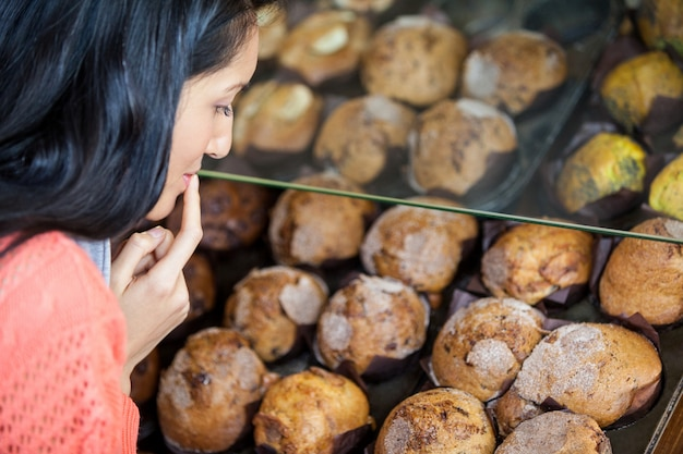 Nachdenkliche frau, die süßes essen auswählt