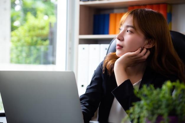 Nachdenkliche frau im büro arbeiten