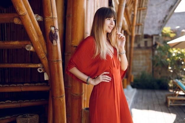 Nachdenkliche frau im orangefarbenen kleid, das in den ferien im tropischen authentischen resort aufwirft
