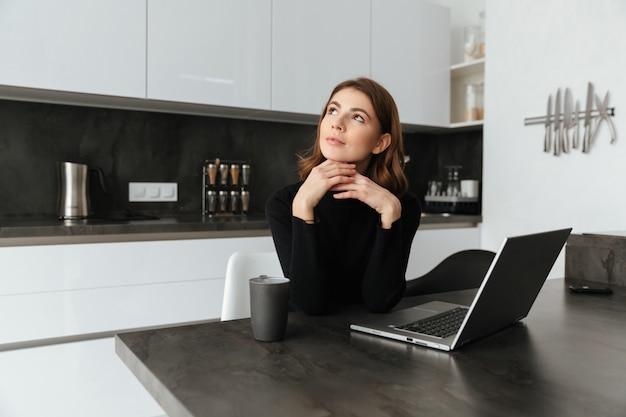 Nachdenkliche frau im schwarzen pullover, der an der küche sitzt