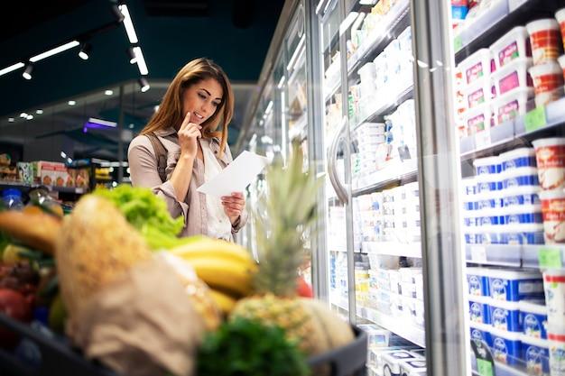 Nachdenkliche frau im supermarkt, die liste hält und einkaufsartikel liest, die sie gerade kauft