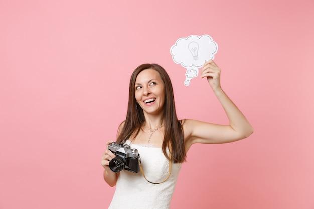 Nachdenkliche frau im weißen kleid hält retro-vintage-fotokamera, sagen sie cloud-sprechblase mit glühbirne, die personal auswählt, fotograf