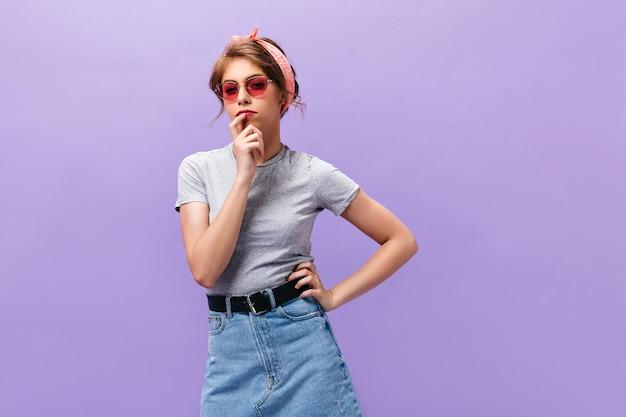 Nachdenkliche frau in der sonnenbrille und im grauen hemd wirft auf lila hintergrund auf. hübsche junge dame im rosa stirnband und in der sommerkleidung, die in die kamera schaut.