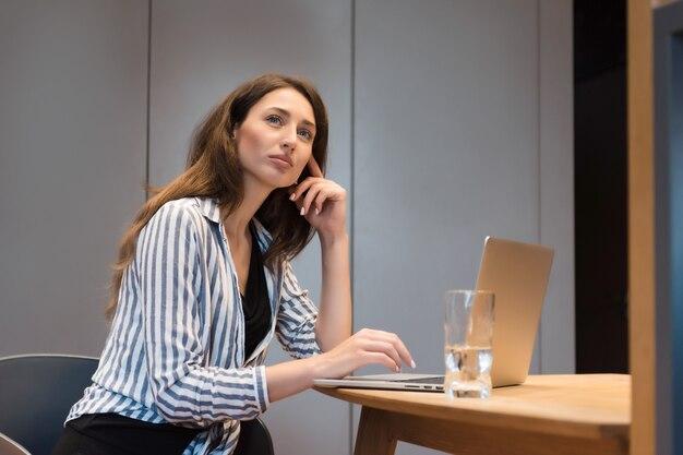 Nachdenkliche frau mit braunen haaren, die mit geöffnetem laptop am tisch sitzt und beiseite schaut