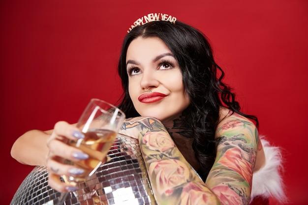 Nachdenkliche frau mit discokugel, die champagner trinkt und aufschaut
