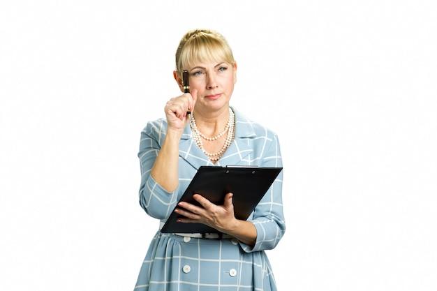 Nachdenkliche frau mit klemmbrett und stift. denkende geschäftsfrau, die zwischenablage und stift gegen weiß hält.