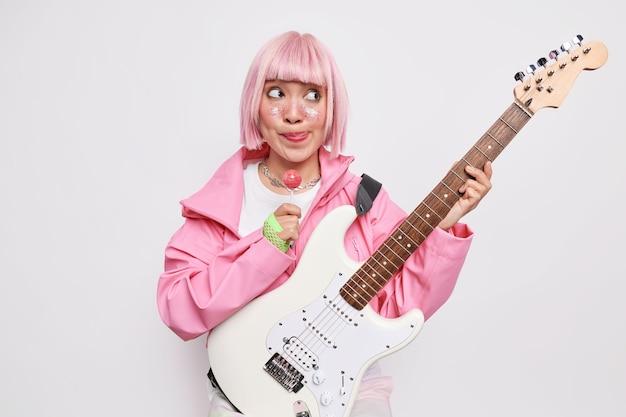 Nachdenkliche frau mit trendiger rosa frisur leckt die lippen hält süße lollipop-posen im innenbereich hält akustische bass-e-gitarre in stilvollem outfit