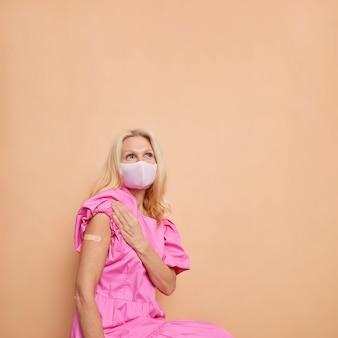 Nachdenkliche frau mittleren alters, die zufrieden ist, nachdem sie eine impfung in die schulter bekommen hat, trägt ein pflaster
