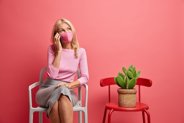 Nachdenkliche frau mittleren alters hat telefongespräch entspannt zu hause auf stuhl trägt schutzmaske während der quarantäne, um zu verhindern, dass krankheit etwas erinnert