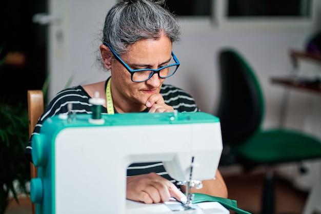 Nachdenkliche frau mittleren alters mit weißen haaren näht mit der nähmaschine zu hause.