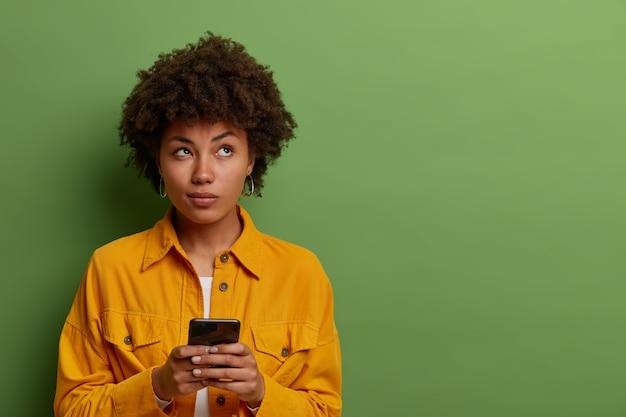 Nachdenkliche frau nutzt moderne anwendung auf dem smartphone, denkt über nachrichteninhalte nach, konzentriert sich oben, bleibt in kontakt mit modernen technologien, gekleidet in modische kleidung, leere stelle an der grünen wand