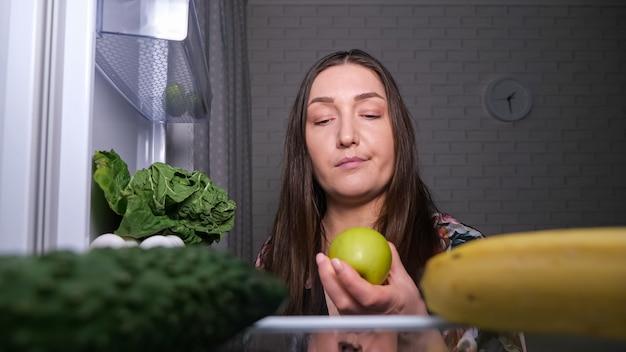 Nachdenkliche frau sucht nach snacks und wählt grünen apfel