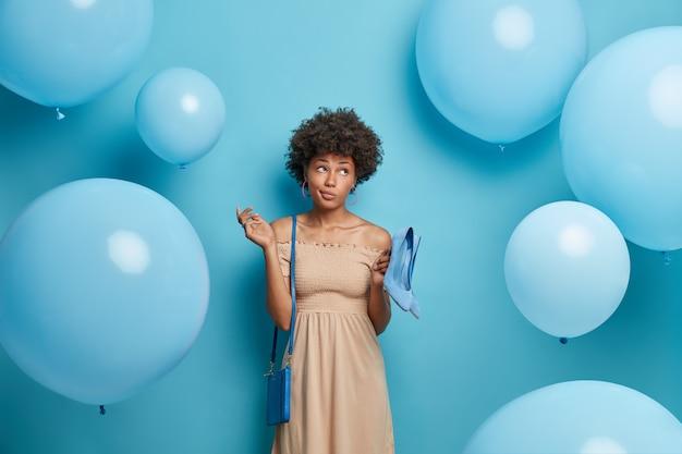 Nachdenkliche frau trägt langes beiges kleid, hält blaue schuhe mit hohen absätzen passend zur tasche, kommt zum jubiläum eines freundes, bereit für ein festliches ereignis, isoliert über blauer wand mit aufgeblasenen luftballons
