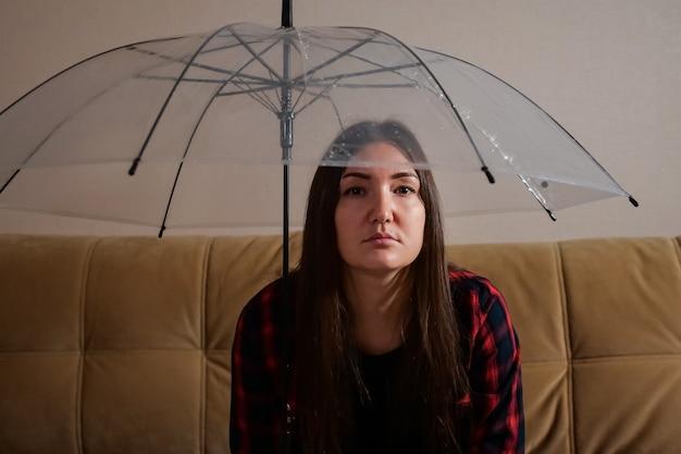 Nachdenkliche frau versteckt sich vor fließendem wasser unter einem klaren regenschirm